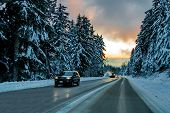 The Icy Winter Road To The Ski Slopes Of Seymour Mountains Passes Through A Snowy Forest, Cars And A poster