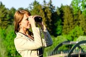 Attractive Young Woman Looking Through Binoculars