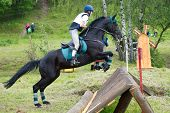 Eventer on horse is overcomes the cross-country fence