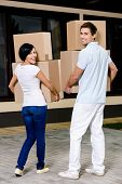 Back view of happy couple carrying cardboard containers while moving to new house