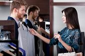 Young man consults with girlfriend while selecting a fashionable shirt