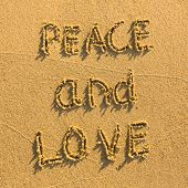 Peace and Love - drawn on the sand of a beach