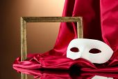 White mask, empty frame and golden silk fabric, on red background