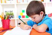 Cute little boy drawing in his album