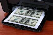Impresora impresión de billetes de dólar falsos sobre fondo de madera