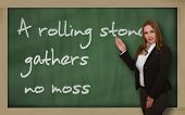 Teacher Showing A Rolling Stone Gathers No Moss On Blackboard