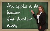 Teacher Showing An Apple A Day Keeps The Doctor Away On Blackboard