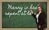 stock photo of repentance  - Successful beautiful and confident woman showing Marry in haste repent at leisure on blackboard - JPG