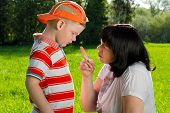 stock photo of misbehaving  - Mother scolding her son with pointed finger in park - JPG
