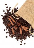 Coffee beans, cinnamon sticks with star anise spice in a hessian drawstring sack  over white backgro