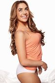 Beautiful joyful young woman with long curly hair wearing an apricot coloured top and smiling at the