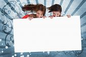 Smiling girls looking down at white copy space screen on blue art deco style background