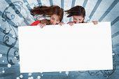 Chicas sonrientes mirando hacia abajo en la pantalla de espacio de copia en blanco sobre fondo de estilo modernista azul
