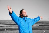 Happy man standing on the beach with hands up on black and white seascape. Concepts like overcoming