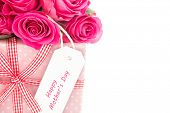 Close up of a bouquet of pink roses next to a pink gift with a happy mothers day card on a white bac