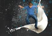 Skateboarder doing an ollie trick with white paint detail on spray painted background