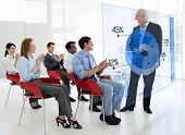 Business people clapping stakeholder standing in front of blue pie chart interface in a meeting
