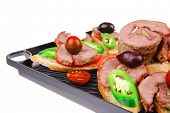 snakes on grill plate : tartlets with sliced meat and supplements isolated over white background