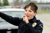 foto of lightbar  - a female police officer talks on the radio with her patrol car in the background - JPG