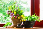 stock photo of tea bag  - sack with bouquet of healing herbs and flowers mortar and pestle on windowsill - JPG