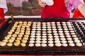 stock photo of dutch oven  - freshly baked traditional Dutch mini pancakes called  - JPG