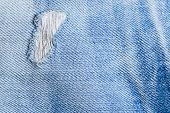 A closeup picture of a part of the jeans that is a bit torn