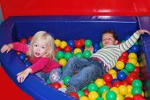 Boy and Girl Playing In The Pool Of Colorful Balls.