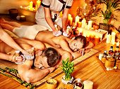 Man and woman getting herbal ball massage in bamboo spa.