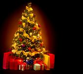 Christmas Tree with Gifts isolated on black background. Beautiful Decorated Christmas Tree with Baubles and Garland