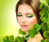 Beautiful Girl with Green Leaves. Fresh Skin. Skincare concept. Nature. Spring Beauty Woman outdoors