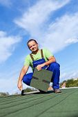 Worker Installs Bitumen Roof Shingles