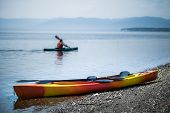 Kayak On The Sea Shore With Kayakers In The Background