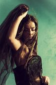 beautiful young woman with black veil in one hand, hair flying across her face, eyes closed, green w