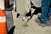 picture of wet pants  - Wet cement sliding down a chute to a worker with shovel - JPG