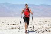 Ultra running man - trail runner in extreme race training for marathon. Fit male athlete running wit