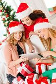 christmas, x-mas, electronics, gadget concept - three smiling women in santa helper hats tablet pc a