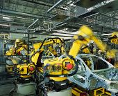 stock photo of production  - yellow robots welding cars in a production line - JPG