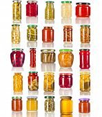 Collection set of many glass bottles with canned preserved food close up isolated on white background