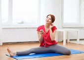 fitness, home, technology and diet concept - smiling teenage girl streching on floor with smartphone