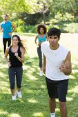 Group of athletes jogging on grassy land in park