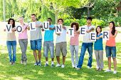 stock photo of united we stand  - Full length of friends holding placards spelling volunteer on campus - JPG