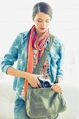 Young pretty woman taking camera from her bag on white background