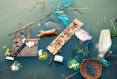 Water pollution with plastic garbage and dirty trash waste. Floating urban debris on contaminated in