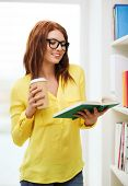 education concept - smiling redhead female student in eyeglasses with book and takeaway coffee in li