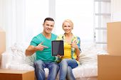 moving, home, technology and couple concept - smiling couple relaxing on sofa and pointing finger to