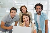 Group of happy business people using laptop together at office desk
