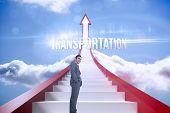 The word transportation and smiling businessman standing against red steps arrow pointing up against