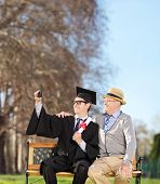 Male student and his proud father taking selfie in park shot with tilt and shift lens