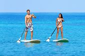 stock photo of paddling  - Stand up paddleboarding beach people on stand up paddle board - JPG