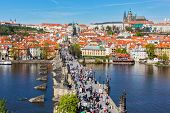 PRAGUE, CZECH REPUBLIC - APRIL 26, 2012:  Charles Bridge over Vltava river crowded with tourists in